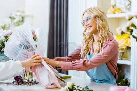 Photo for Beautiful smiling female florist in glasses giving bouquet to customer in flower shop - Royalty Free Image
