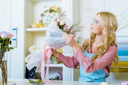 Photo for Beautiful female florist in glasses arranging bouquet in flower shop - Royalty Free Image