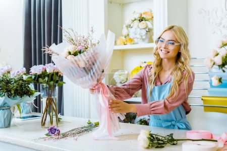 Photo for Beautiful smiling female florist in glasses holding flower bouquet at counter in flower shop - Royalty Free Image