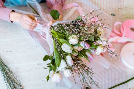 Photo for Top view of female florist arranging bouquet with tulips and roses on table - Royalty Free Image
