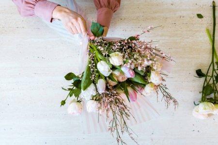 Photo pour Vue de dessus du fleuriste femelle arrangeant bouquet de tulipes blanches et roses sur la table - image libre de droit