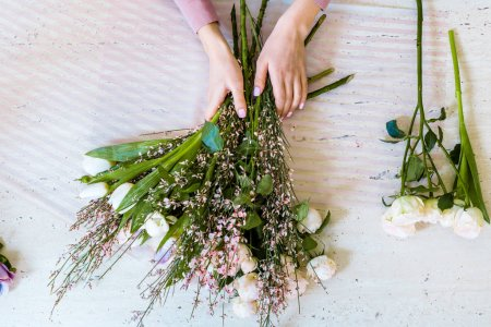 Photo for Top view of female florist arranging bouquet with white tulips and roses on table - Royalty Free Image