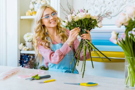 Photo for Attractive smiling female florist in glasses arranging bouquet in flower shop with tools on counter - Royalty Free Image