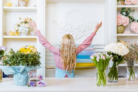 Photo for Back view of female florist with hands in air in flower shop - Royalty Free Image