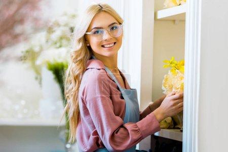 Photo pour Mise au point sélective de belle fleuriste femme souriante dans des verres tenant jaune bouquet de fleuriste - image libre de droit