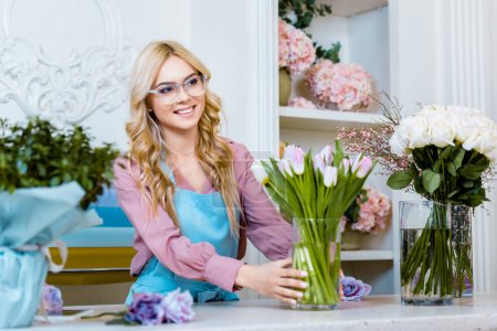 Photo for Beautiful smiling female florist holding vase with pink tulips in flower shop - Royalty Free Image