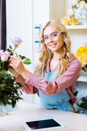 Photo for Beautiful female florist putting pink rose in bouquet and looking at camera in flower shop - Royalty Free Image