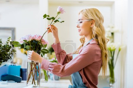 Photo for Beautiful female florist putting pink rose in bouquet in flower shop - Royalty Free Image