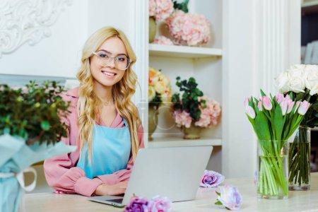 Foto de Dueño de la tienda de flor hembra hermosa en copas sentado en el escritorio, mirando a cámara y uso de ordenador portátil - Imagen libre de derechos