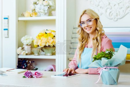 Photo for Beautiful female flower shop owner in glasses looking at camera and using digital tablet at counter - Royalty Free Image