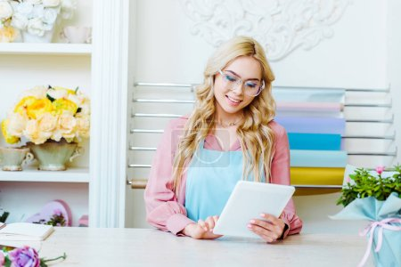 Photo for Beautiful smiling female flower shop owner in glasses using digital tablet at counter - Royalty Free Image