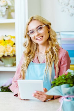 Photo for Beautiful smiling female flower shop owner in glasses looking at camera and using digital tablet at counter - Royalty Free Image