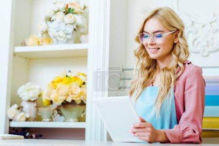 Photo pour Foyer sélectif de belle propriétaire de magasin de fleurs femelles dans des lunettes en utilisant la tablette numérique - image libre de droit