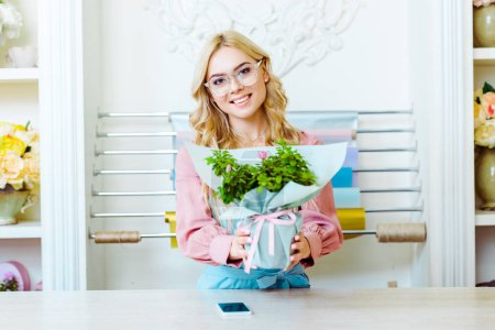 Photo for Beautiful female florist in glasses looking at camera and presenting bouquet in flower shop - Royalty Free Image