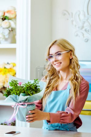 Photo for Beautiful smiling female florist in glasses presenting bouquet in flower shop - Royalty Free Image