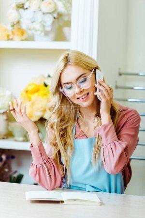 Foto de Beautiful smiling female flower shop owner in glasses talking on smartphone and holding pencil - Imagen libre de derechos