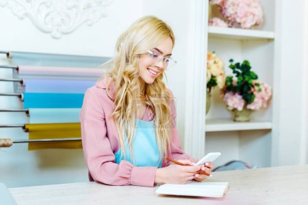 Photo for Beautiful smiling female flower shop owner in glasses using smartphone at counter - Royalty Free Image