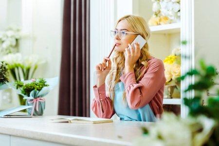 Foto de Dueño de la tienda de flor hembra hermosa en gafas hablando en teléfono inteligente y sostener el lápiz - Imagen libre de derechos