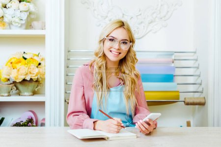 Foto de Beautiful smiling female flower shop owner in glasses writing in notebook, using smartphone and looking at camera - Imagen libre de derechos