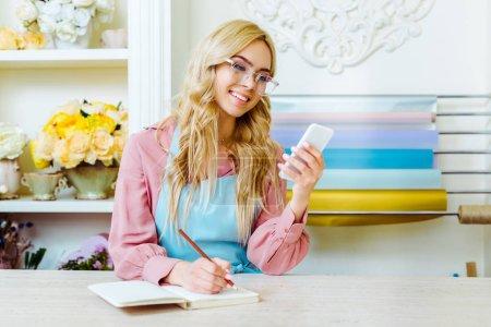 Foto de Beautiful smiling female flower shop owner in glasses writing in notebook and using smartphone - Imagen libre de derechos