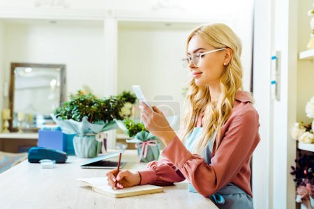 Foto de Beautiful female flower shop owner in glasses writing in notebook and using smartphone - Imagen libre de derechos