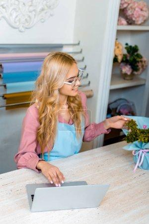 beautiful smiling female florist in glasses using laptop in flower shop