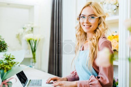 Foto de Hermosa mujer Floreria en vasos utilizando la computadora portátil en la tienda de flores y mirando a cámara - Imagen libre de derechos