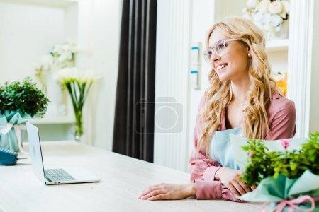 Foto de Hermosa mujer Floristerias en gafas sonriendo y sentado en el escritorio de la computadora en la tienda de la flor - Imagen libre de derechos