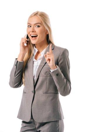 Photo pour Femme d'affaires gai vu idée et pointant vers le haut tout en parlant sur smartphone isolé sur blanc - image libre de droit