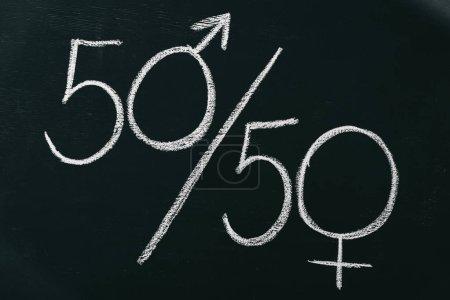 Photo pour Signes masculins et féminins comme 50 à 50 pourcents sur tableau noir, le concept de l'égalité entre les sexes - image libre de droit