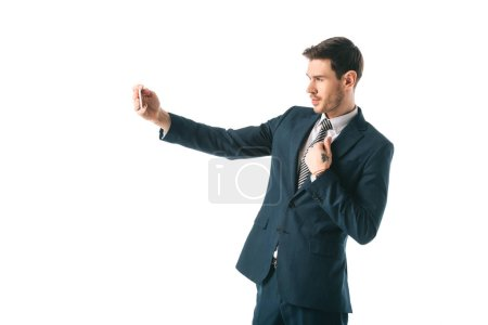 Photo for Handsome businessman taking selfie on smartphone isolated on white - Royalty Free Image