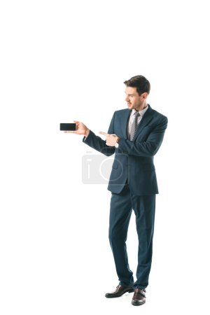 businessman in suit pointing at blank screen on smartphone, isolated on white