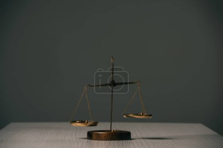 Photo for Empty scales of justice on wooden table on grey - Royalty Free Image