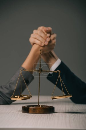 Photo for Selective focus of business colleagues arm wretsling on wooden table with scales of justice on grey - Royalty Free Image