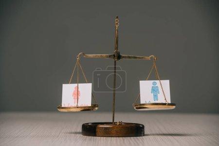 Photo pour Symboles masculins et féminins sur les échelles sur table en bois sur gris, concept d'égalité des sexes - image libre de droit