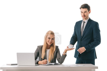 handsome secretary brought cup of coffee for smiling businesswoman at workplace with laptop, isolated on white