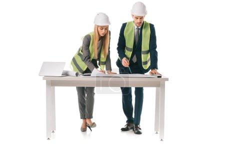 Photo pour Ingénieurs en gilets de sécurité et casques travaillant avec plans, isolés sur blanc - image libre de droit