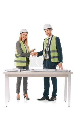 Photo pour Architectes en gilets de sécurité et casques serrant la main, isolés sur blanc - image libre de droit