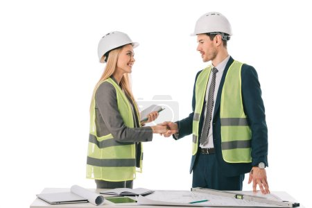 Photo for Architects in safety vests and hardhats making deal and shaking hands, isolated on white - Royalty Free Image