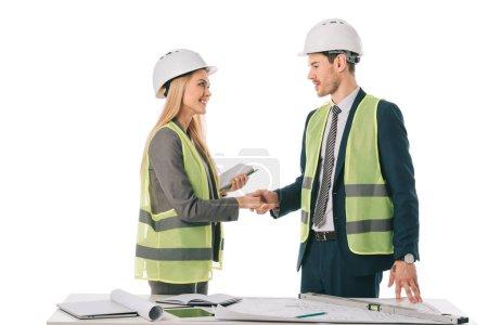 Photo pour Architectes en gilets de sécurité et casques faisant face et se serrant la main, isolé sur blanc - image libre de droit