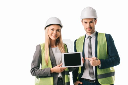 Foto de Architects in safety vests and hardhats showing new project on digital tablet, isolated on white - Imagen libre de derechos