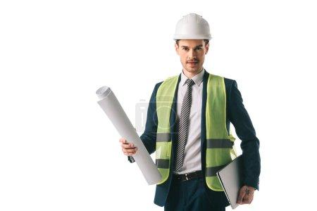 Photo pour Beau male architecte au gilet de sécurité et casque tenant blueprint et portable, isolé sur blanc - image libre de droit