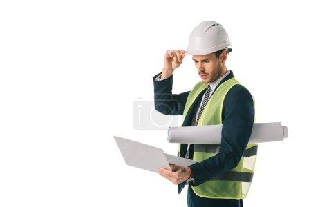 Photo pour Ingénieur mâle au gilet de sécurité et casque maintenez blueprint et avec ordinateur portable, isolé sur blanc - image libre de droit