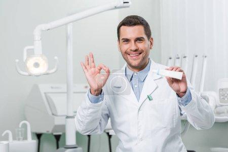 Photo pour Dentiste tenant dentifrice et montrer signe OK en clinique dentaire - image libre de droit