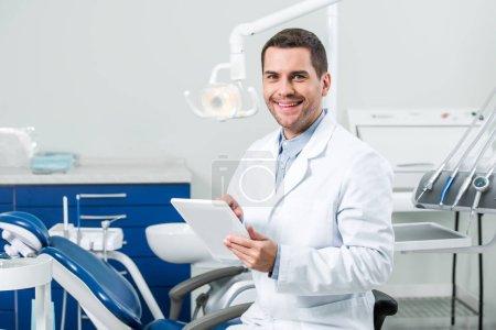 Photo pour Dentiste heureux en manteau blanc tenant tablette numérique dans la clinique dentaire - image libre de droit