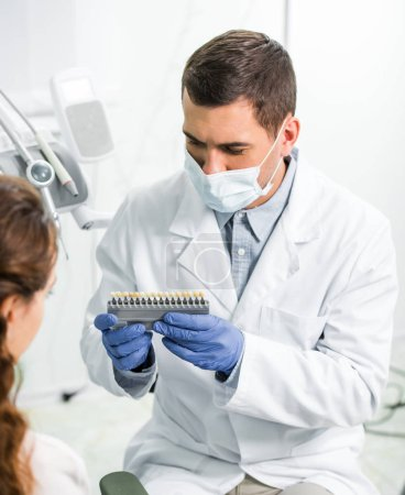 woman selecting teeth color palette near dentist in mask and latex gloves