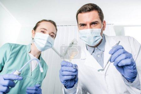 Photo pour Dentistes en masques tenant des instruments dentaires dans les mains - image libre de droit