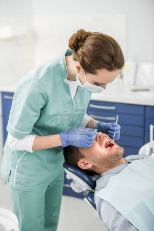 Photo for Female dentist in mask and latex gloves examining patient with opened mouth - Royalty Free Image