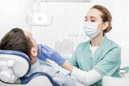 Photo pour Dentiste détenant des instruments dentaires près du patient dans une clinique dentaire - image libre de droit