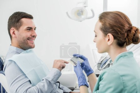 happy man pointing with finger at teeth color palette in hands of dentist